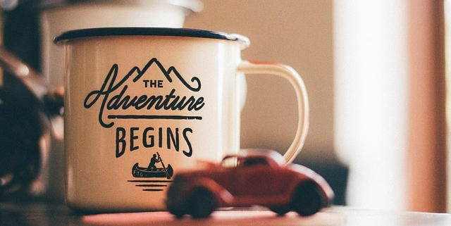 Coffee mug with text saying the adventure begins