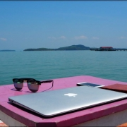 Laptop on a table near the sea - very sunny